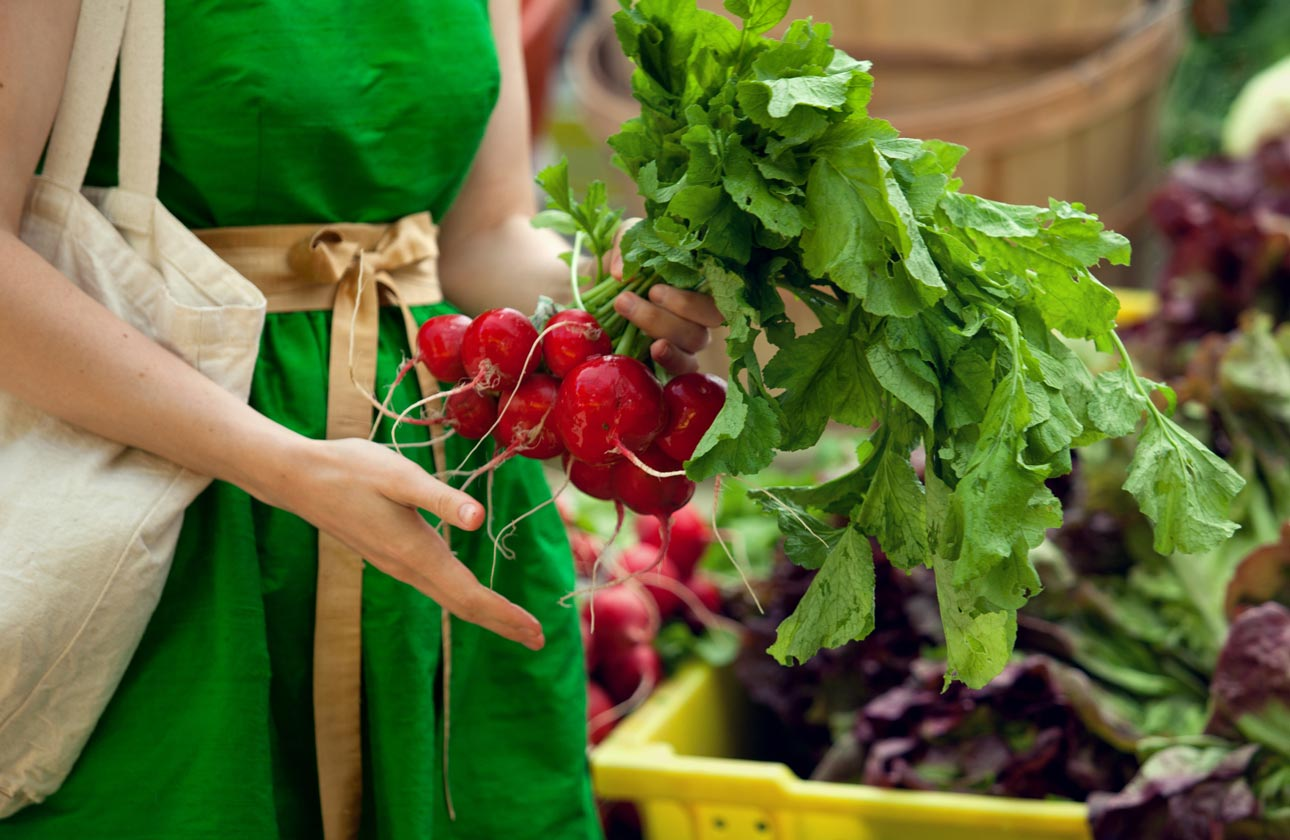 A woman in a green dress holding radishes
