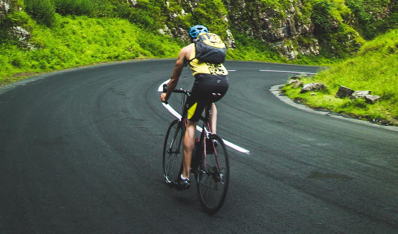 A man riding his bike on a paved road