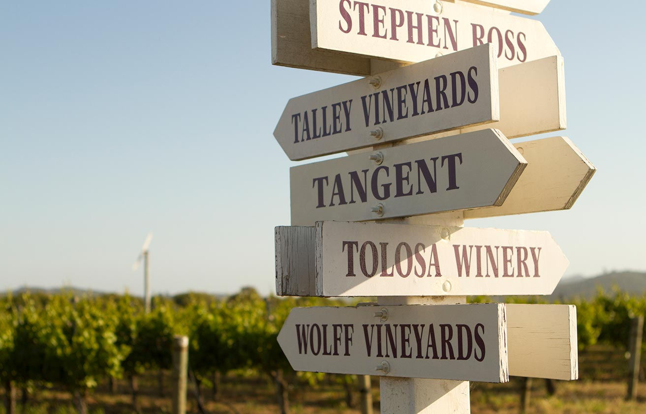 Signs pointing to Stephen Ross, Talley Vineyards, Tangent, Tolosa Winery, and Wolff Vineyards