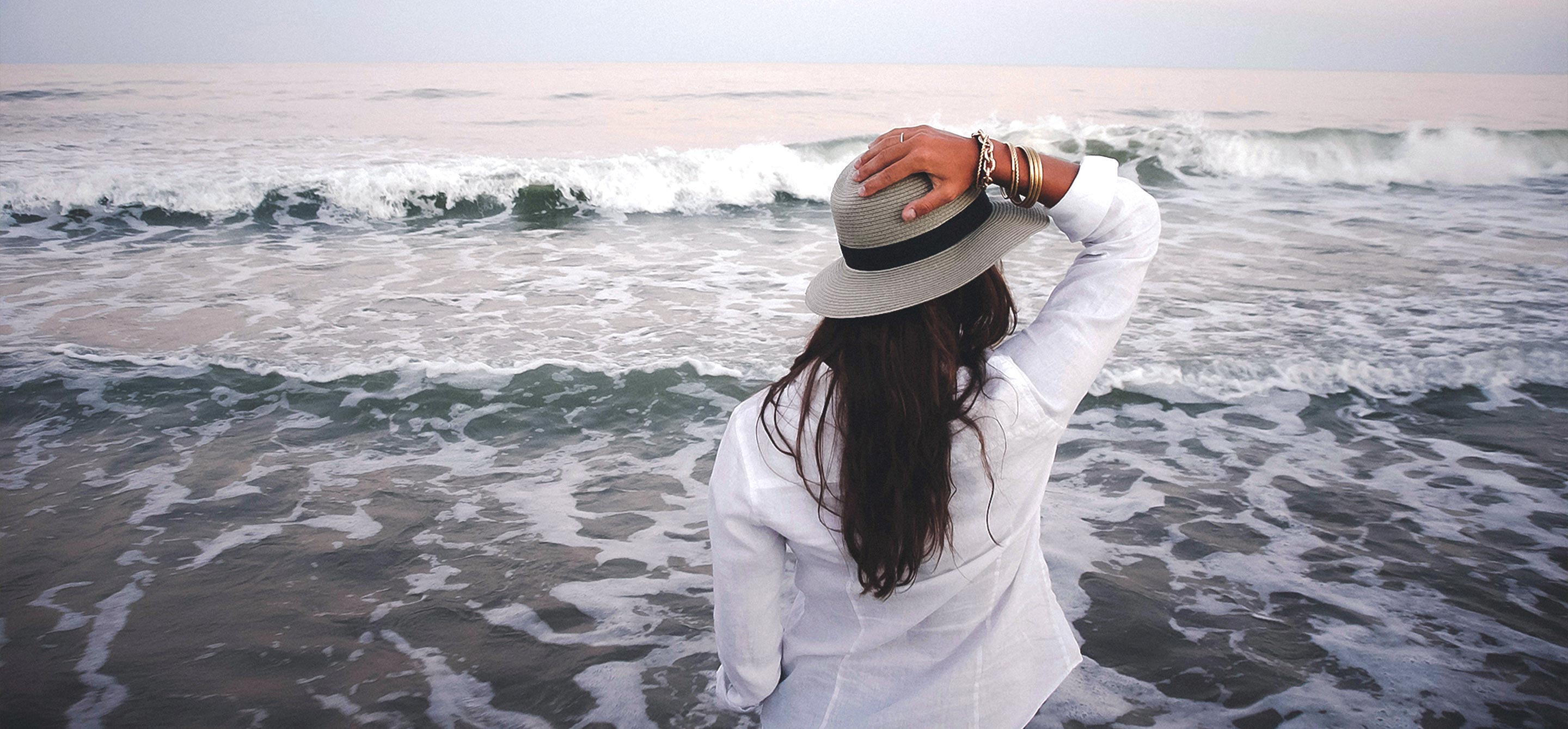 Woman holding her hat with ocean waves coming in